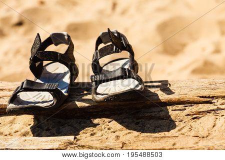 Summertime footwear concept. Closeup shot of black sandals shoes on sandy beach