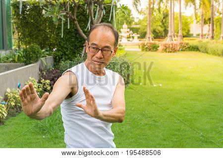 Asian senior man wear white shirt stand and practice tai chi on the grass in the park and copy space
