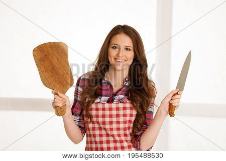 Beautiful Young Woman Holding Wooden Bord And Knife In Kitchen