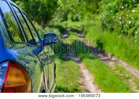 The blue car is parked on a forest road. Focus on the car
