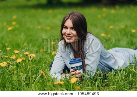 Woman With Takeaway Drink In Park