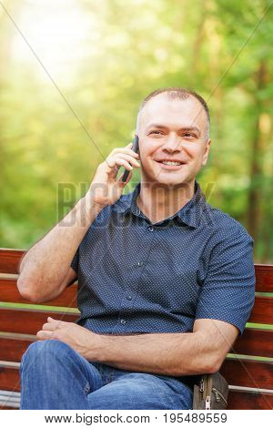 Adult Man Around 35-40 Is Talking With Smile By Phone At Summer Park