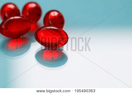 Close-up of red painkiller pills on a blue background.