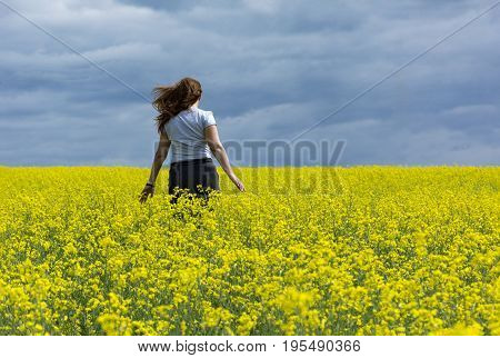 girl one 1 runs in a field of yellow rapeseed against the blue sky the horizon