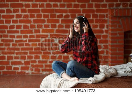 Woman listening wireless music with headphones from a smart phone at home.