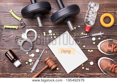 Sport equipment, steroids, wooden floor. Gavel, syringe, pills, dumbbells, water, footwear, message on wooden background.