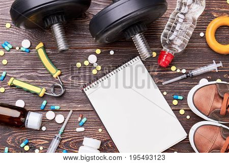 Empty notebook, syringes, pills, dumbbells. Pharmaceutical preparations and sport equipment on wooden background.