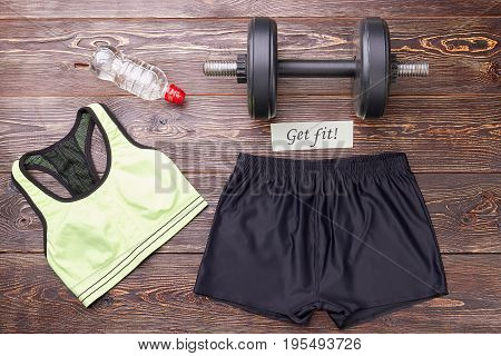 Female accessories for sport training. Top, shorts, dumbbell, bottle, message. Women sport activity.