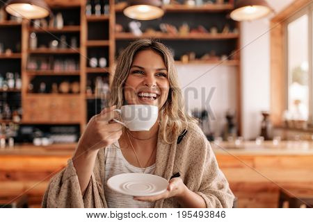 Portrait of beautiful young woman standing in a cafe and drinking coffee. Smiling young female having coffee in a restaurant.