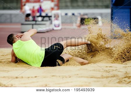male athlete jumping long jump landing in athletics