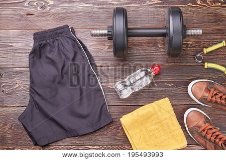 Equipment for men weight lifting. Shorts, dumbbell, expander, bottle, towel, sneakers. Always be in shape.
