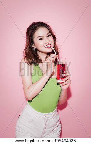 Celebrating asian woman drinking red softdrink on pink background