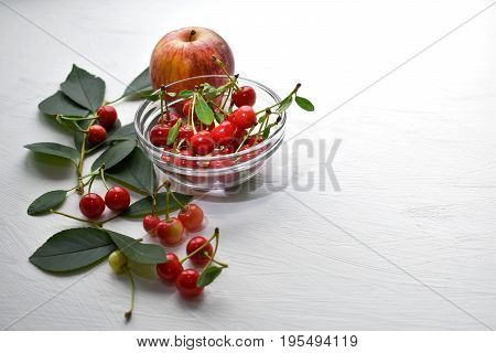 Composition with apple and cherry. White background. Bright red.