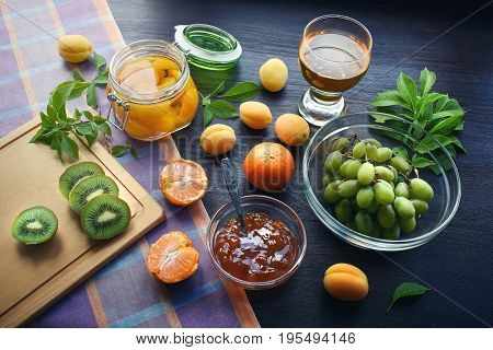 Composition from fruits. Apricot compote. Kiwi, juice, jam, tangerines.