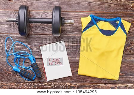 Athletic clothes and sport equipment. Message, jumping rope, dumbbell, t-shirt on wooden background. Be stronger and healthier with gym workout.