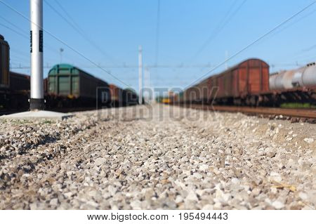 Close Up Narrow Shot Of A Railway Stones And Rocks Close To Freight Train At The Italian Train Depot