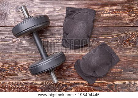 Dumbbell, elbow pads, wooden floor. Protectors for elbows, vintage background. Be in safety.