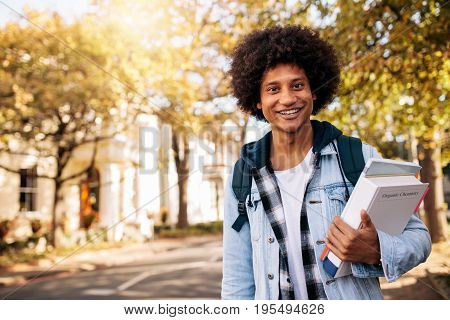 Young afro american student returning from college. Young male university student with book in college campus.