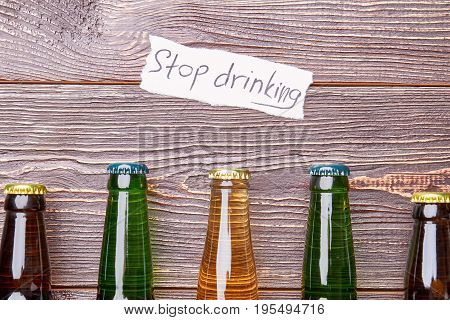Life without alcohol drinking. Several bottles with alcohol, paper message above it.