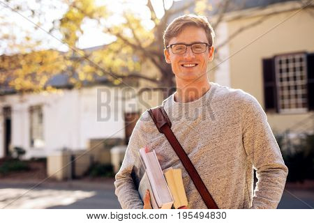 Happy male college student outdoors with books. Young university student with books in campus.
