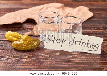 Two glass shots with alcohol. Pickled cucumbers, transparent shots, message, retro background.