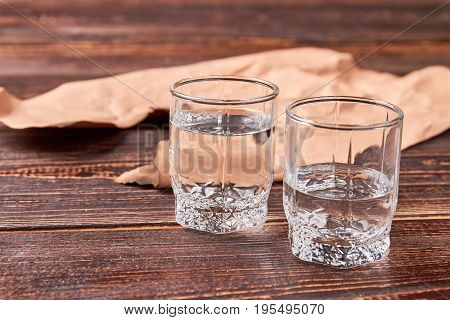 Two transparent glass shots with vodka. Concept of addiction to alcohol.