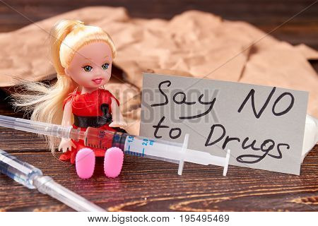 Syringes, doll, message on blurred background. Say no drugs and harmful habits.