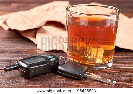 Glass of whisky, car keys, paper. Alcohol in transparent glass, automobile keys, vintage paper on wooden background.