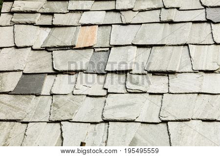 Textures and patterns consept. Detailed closeup background wall made of grey stone rocks.