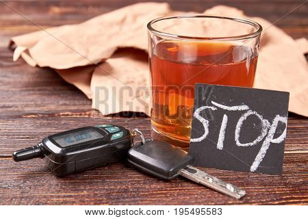 Alcohol beverage, car keys, note. Brown alcohol beverage in glass, car keys, message stop on wooden background. How to stop alcohol drinking concept.