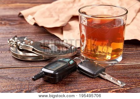 Handcuffs, car keys, whisky glass. Glass of alcohol, metal handcuffs, keys close up. Driver and alcohol is big irresponsibility.
