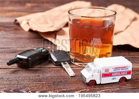 Alcohol, keys, ambulance, wooden background. Glass of whiskey, keys, car ambulance. Drinking alcohol beverage and hospitalization by emergency ambulance.