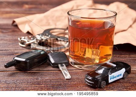 Whiskey, keys, handcuffs, police car. Car key on the bar with spilled alcohol. Alcohol beverage and judgment of police.
