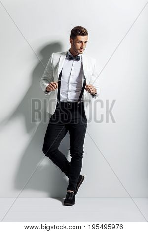 Full length portrait of handsome stylish man in white elegant suit posing and leaning at wall