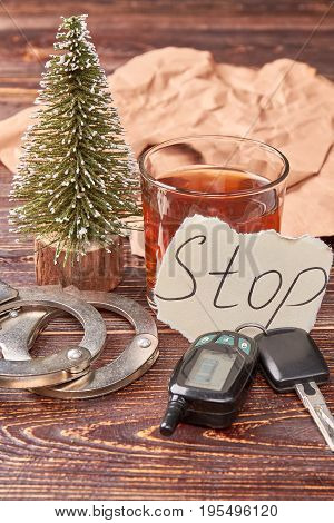 Composition from whiskey, keys and handcuffs. Car keys, handcuffs, message stop, glass of alcohol on wooden background.