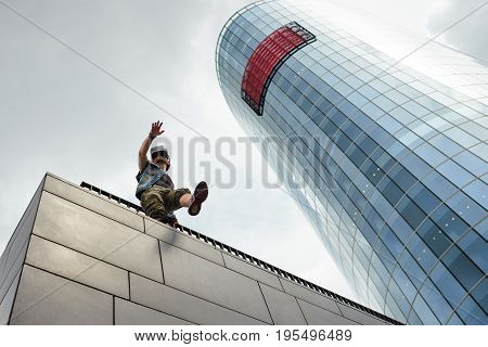 Low angle view of man in stylish clothes walking on the edge of modern building wearing VR glasses with head-mounted display obsessed with augmented reality moving carelessly almost falling down