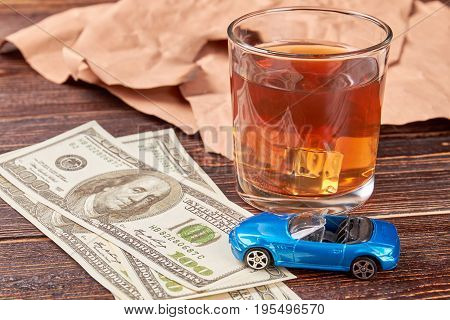 Money and whiskey on wooden background. Dollars, car, glass of alcohol close up. The concept of drink and driving.
