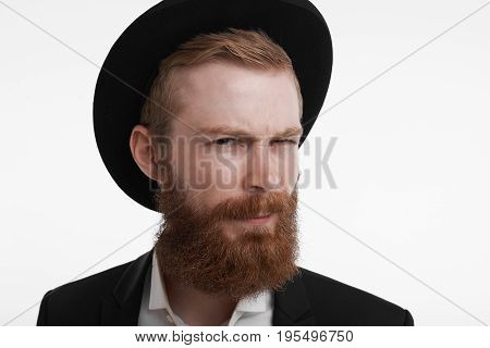 Human emotions feelings reaction and attitude. Close up portrait of attractive hipster with thick red beard wearing fashionable black hat frowning looking at camera in distrust and suspicion