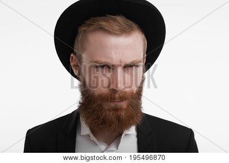 Headshot of handsome stylish unshaven young European redhead man wearing suit and trendy hat looking at camera having suspicious disrtustful facial expression pursuing lips and narrowing eyes