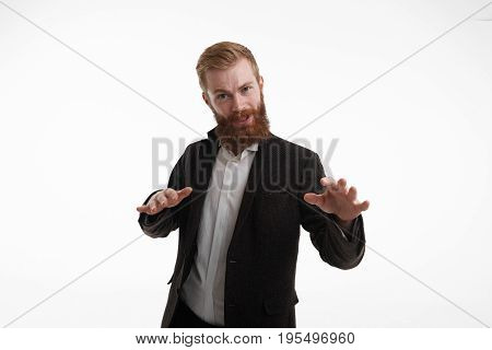 Bearded businessman with attitude wearing formal suit standing at white wall gesturing with hands as if saying Calm dowm or Relax. Negative human emotions facial expressions signs symbols