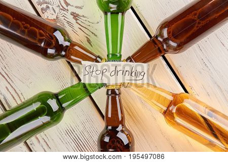Do not be loser, stop drinking. Set of colorful bottles of alcoholic beverages, wooden table.
