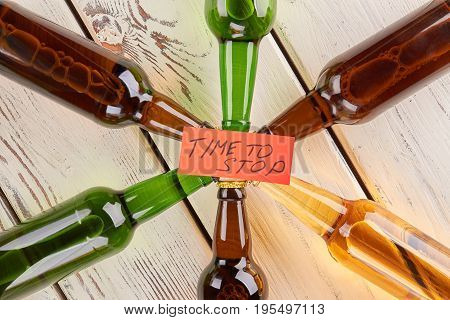 Alcohol dependence dangerous for life. Composition of bottles, wooden background.