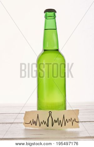 Abuse of alcohol harmful for heart. Image of cardiac impulses, bottle of beer.