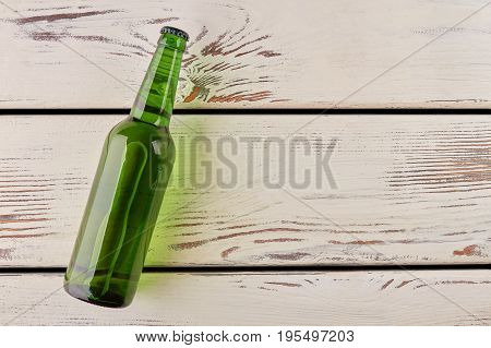 Bottle lies on wooden background. Full bottle of alcohol and copy space.