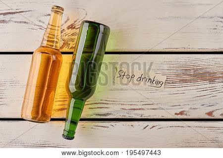 Bottles of beer in different position. Stop drinking and start thinking.