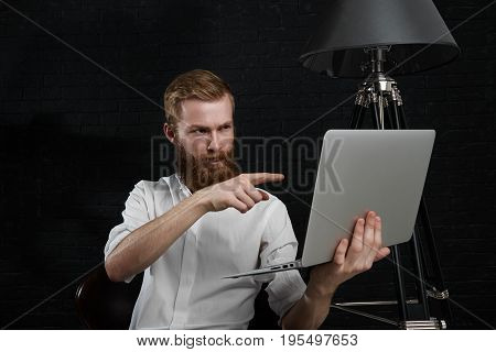 People photographing occupation job and technologies concept. Studio shot of stylish bearded photographer holding generic laptop pc and pointing index finger at screen showing something on it