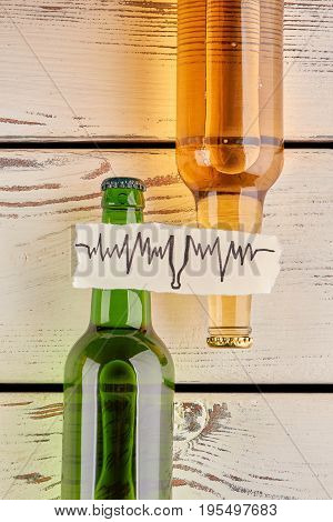 How alcohol affects your body. Vertical image of bottles with beer, wooden background.