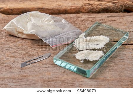 Illegal narcotic preparations, wooden background. Overdose of drugs leads to death.