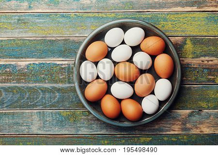 White and brown chicken eggs in vintage bowl on rustic wooden table from above. Organic and farm food.