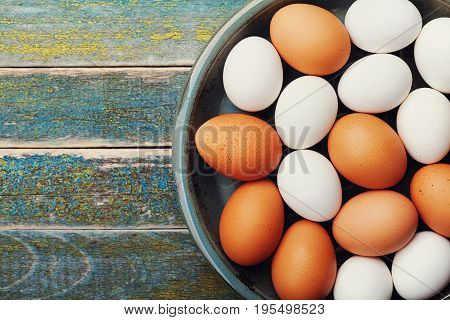White and brown chicken eggs in vintage bowl on rustic wooden table top view. Organic and farm food.